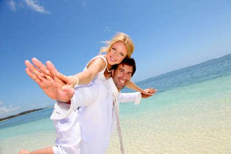 beach wedding: Groom holding bride on his back Stock Photo
