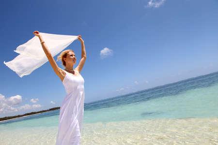 destination wedding: Bride on the beach with white stole