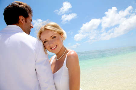 Just-married couple standing by blue lagoon Stock Photo - 11503451