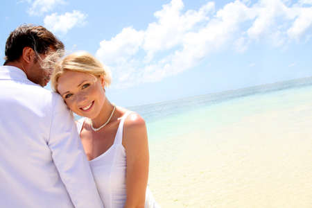 beach wedding: Just-married couple standing by blue lagoon Stock Photo