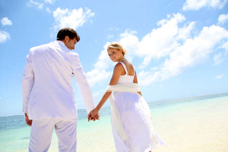 Just-married couple standing by blue lagoon Stock Photo