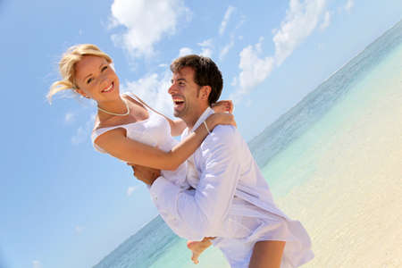 beach wedding: Groom and bride laughing on a sandy beach
