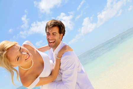 Groom and bride laughing on a sandy beach Stock Photo - 11503115