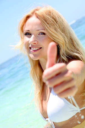 Beautiful blond woman in the sea showing thumbs up photo