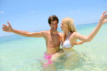 personas abrazadas: Pareja disfrutando de las vacaciones en la playa