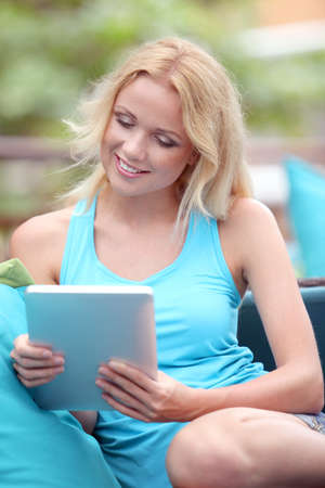 Beautiful blond woman websurfing with electronic tablet photo