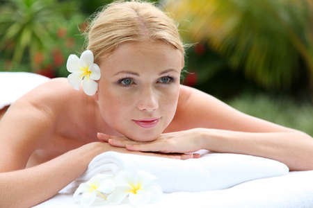 lying down: Portrait of beautiful blond woman relaxing on massage bed