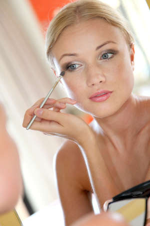 putting up: Portrait of beautiful woman applying eyeshadow