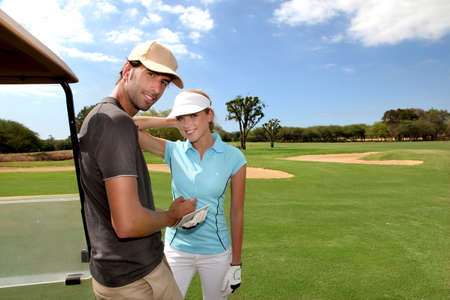 Couple on golf course with cart photo