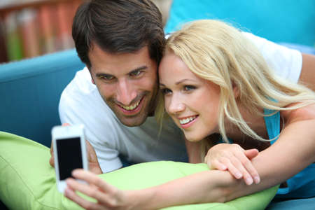 Couple taking picture of themselves with mobile phone photo