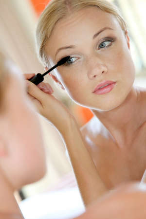 Portrait of young woman putting mascara on photo