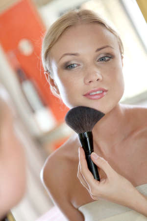 Portrait of blond woman applying powder on her face photo