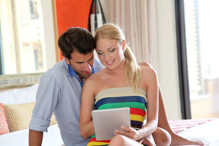 android tablet: Couple using electronic tablet in hotel room