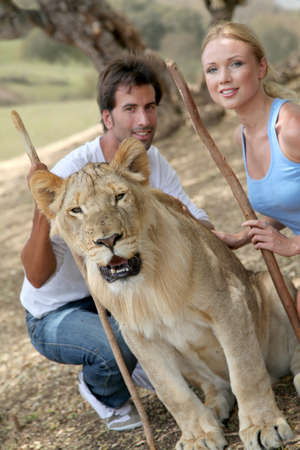 african safari: Couple sitting by lion in Savannah