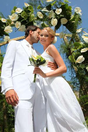 Groom kissing bride on wedding day photo