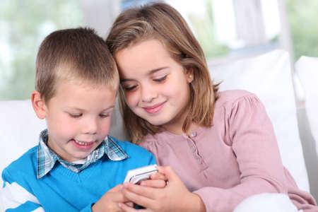 Bambini che giocano con lo smartphone Archivio Fotografico