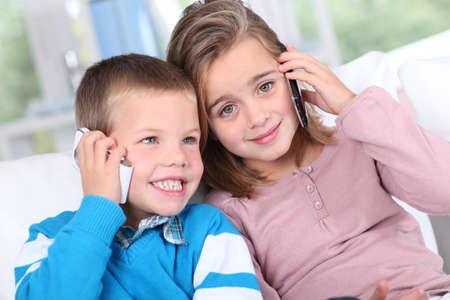 ni�os hablando: Retrato de los ni�os que hablan por tel�fono m�vil