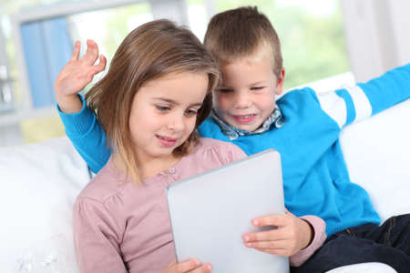 Children using electronic tablet at home photo