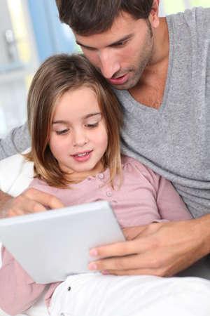 personas abrazadas: Padre e hijo que usa la tableta electrónica en el hogar