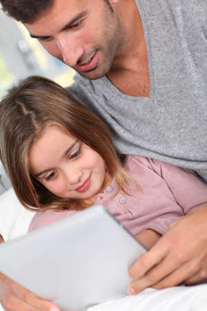 Father and child using electronic tablet at home Stock Photo - 11517723