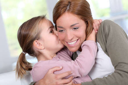 personas abrazadas: Retrato de niña besando a su madre Foto de archivo