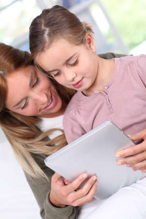 tabs: Mother and child using electronic tablet at home