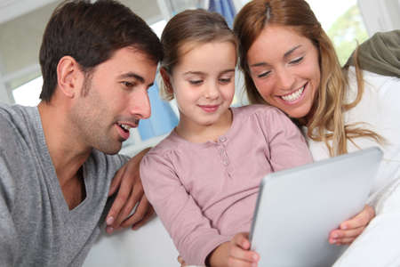 Family using electronic tablet at home photo