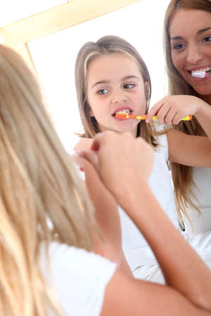 Mother and daughter brushing their teeth photo