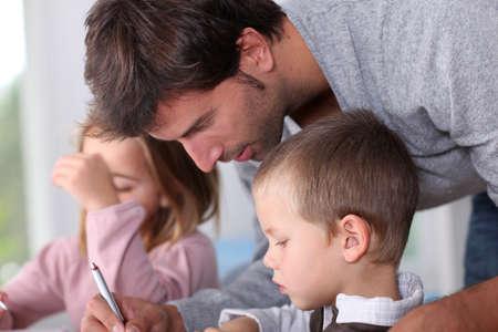 Man helfen Kindern bei den Hausaufgaben