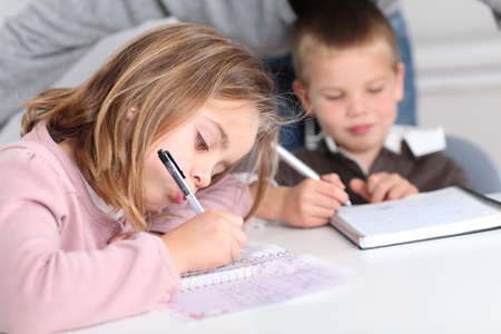 niños escribiendo: Los niños en la escuela haciendo su tarea