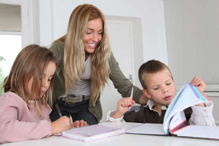 kids learning: Woman helping kids with homework