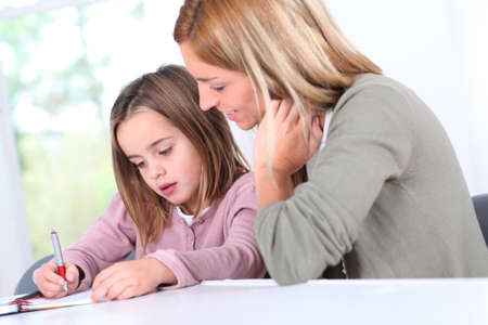 Mother and daughter doing homework at home photo