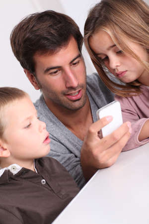 mobilephone: Father and children playing with smartphone