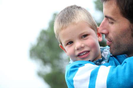 personas abrazadas: Retrato de niño en los brazos de papá celebración Foto de archivo