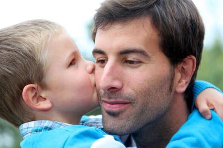 Little boy giving daddy a kiss photo