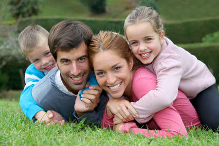 family holidays: Portrait of happy family lying down in grass Stock Photo