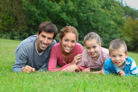 Portrait of happy family lying down in grass photo