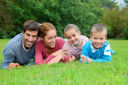 family garden: Portrait of happy family lying down in grass Stock Photo