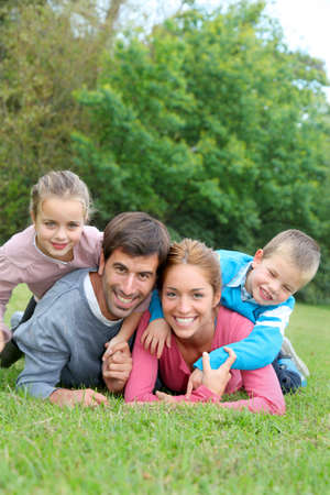 family grass: Portrait of happy family lying down in grass Stock Photo