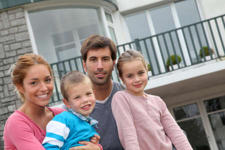 fachada de casa: Feliz familia de 4 personas que se sientan frente a la casa nueva