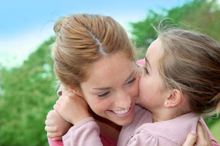 Portrait of little girl giving kiss to her mom photo