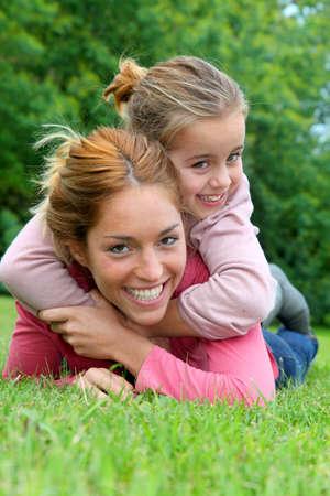 personas abrazadas: La niña y la madre por sobre la hierba en el parque Foto de archivo