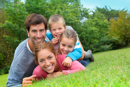 family garden: Portrait of happy family laying in country field