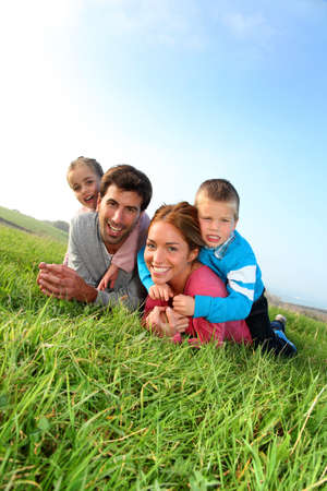 Portrait of happy family laying in country field photo