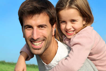 personas abrazadas: Retrato del padre dando caballito a su hija