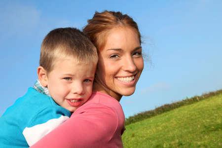 personas abrazadas: Mujer con hijo a la espalda