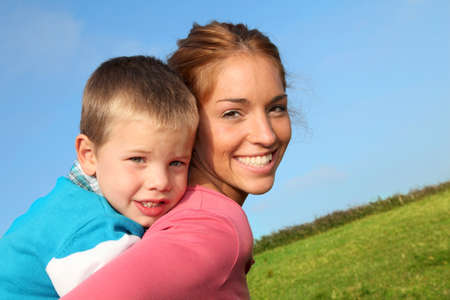 piggyback ride: Woman holding son on her back Stock Photo