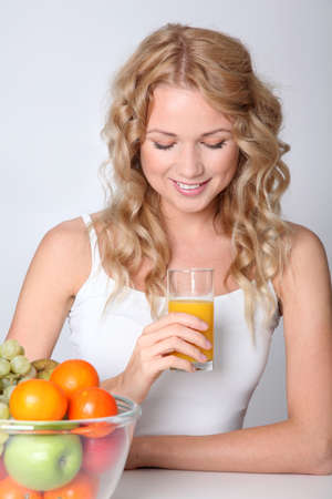 Beautiful blond woman drinking fruit juice Stock Photo - 11517920