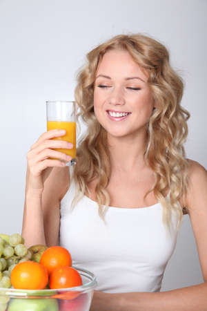 Beautiful blond woman drinking fruit juice Stock Photo - 11517985