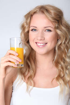 Blond woman drinking orange juice Stock Photo - 11517863
